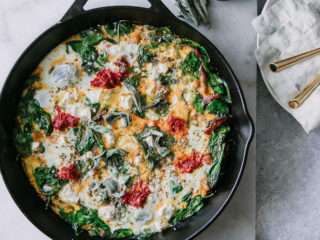 a frittata with spinach, red harrisa sauce, and feta cheese in a black cast iron skillet on a white table with a white napkin and a plate with gold forks