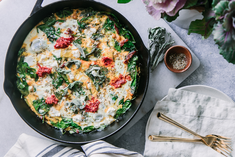 a frittata in a cast iron skillet on a white marble table with a bowl of sea salt and fresh sage leaves