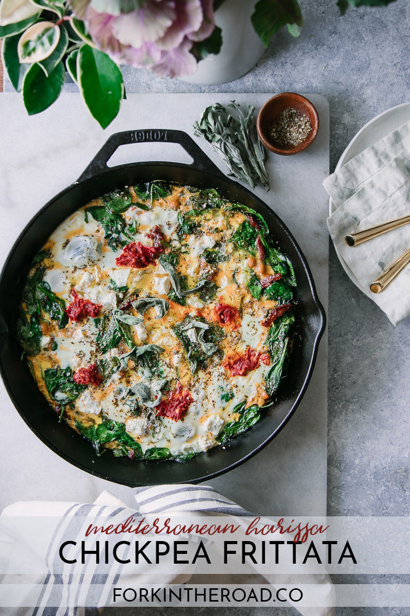 "a spinach frittata in a cast iron skillet with feta cheese and red harissa and the words ""mediterranean chickpea harissa frittata"" in black writing"