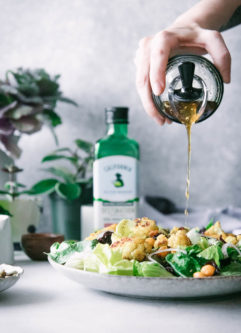 a hand drizzling salad dressing onto a salad on a white table