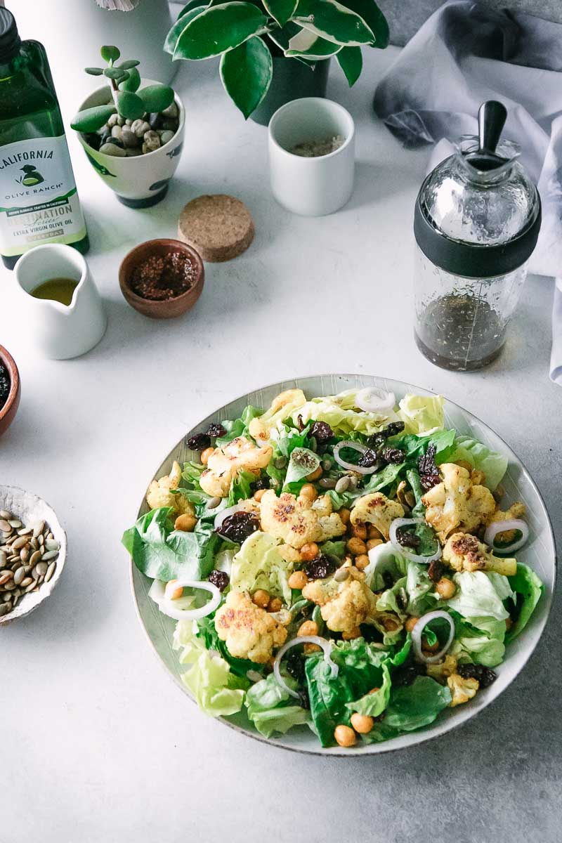 a salad with cauliflower and chickpeas on a white table with small bowls and saucers holding spices and oils