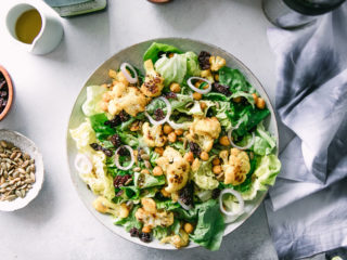 a simple greens salad with cauliflower and chickpeas on a white plate on a table with a blue napkin