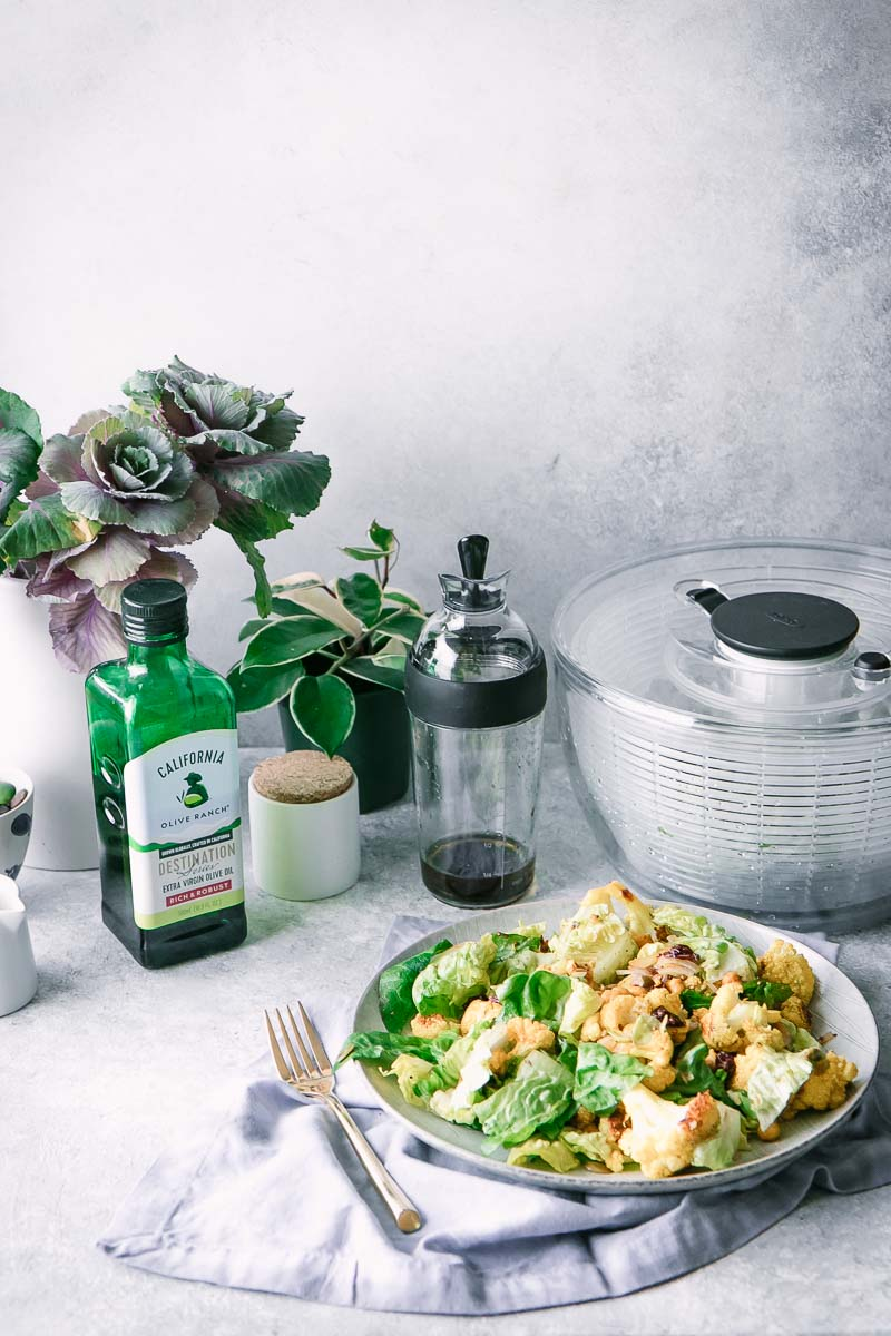 a salad, salad spinner, salad dressing shaker, bottle of olive oil, and vase with flowers on a white table