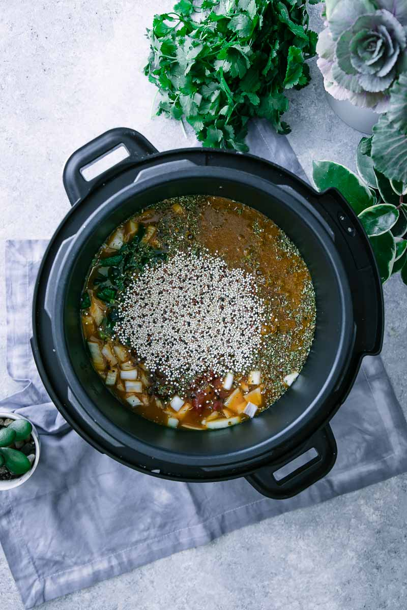 an instant pot pressure cooker filled with vegetable broth, vegetables, and quinoa