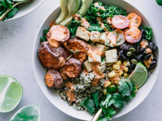 "quinoa, black beans, corn, kale, tomatoes, roasted sweet potatoes, sliced avocado, a lime wedge, and cilantro in a white bowl on a white countertop with lime wedges and cilantro leaves, and the words ""chipotle lime black bean bowl"" in black writing with green and yellow highlight"