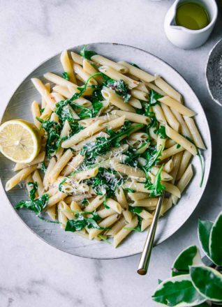penne, arugula, and lemon pasta on a white plate with a gold fork on a marble countertop with a green plant