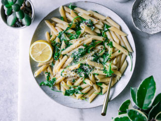 a plate of penne pasta with spinach and a slice of lemon on a white table with a bowl of parmesan cheese