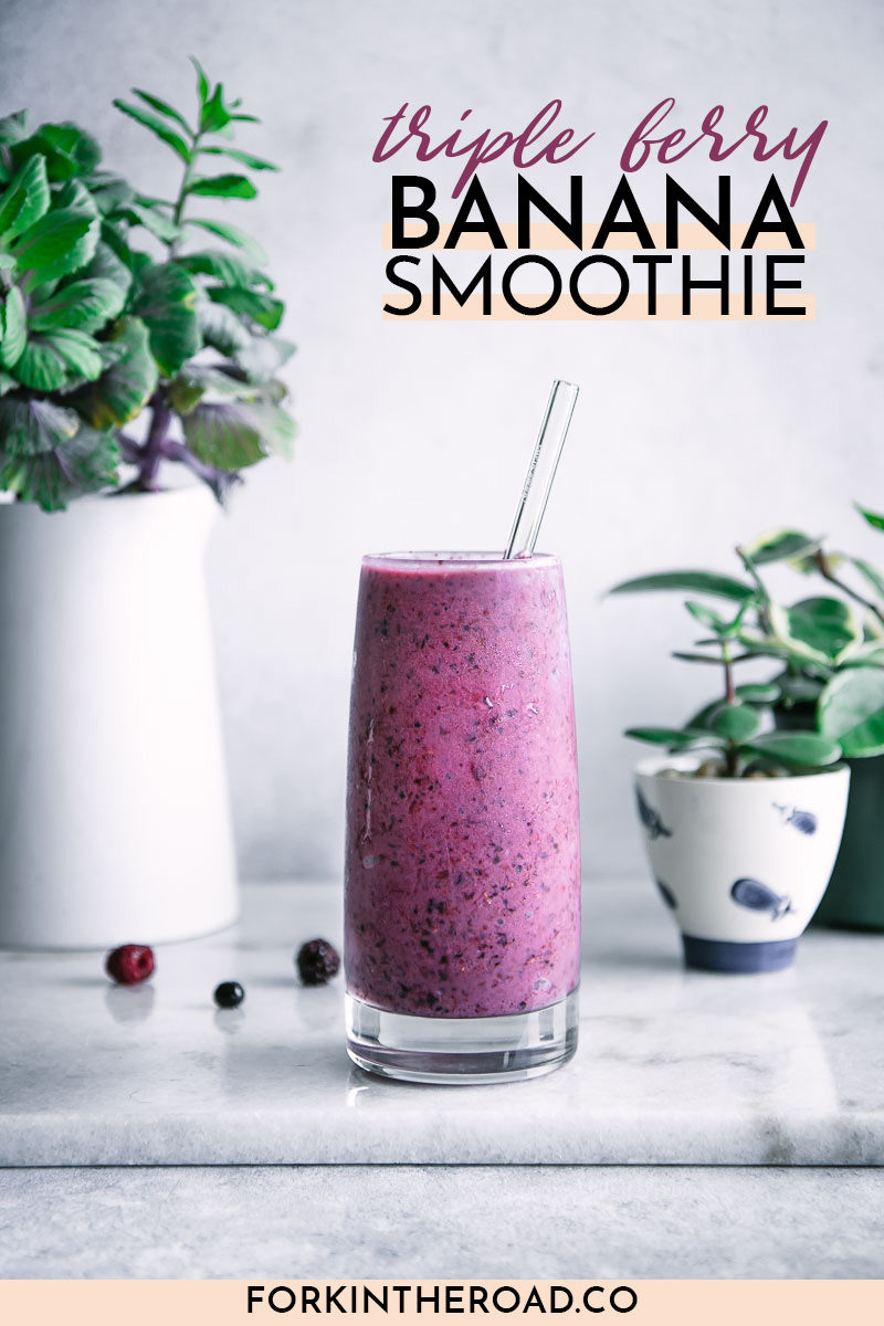 "a purple smoothie on a white table with the words ""triple berry banana smoothie"" in black writing"