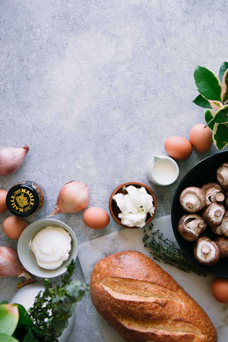 bread, eggs, mushrooms, goat cheese, cream, shallots, and mustard on a blue table