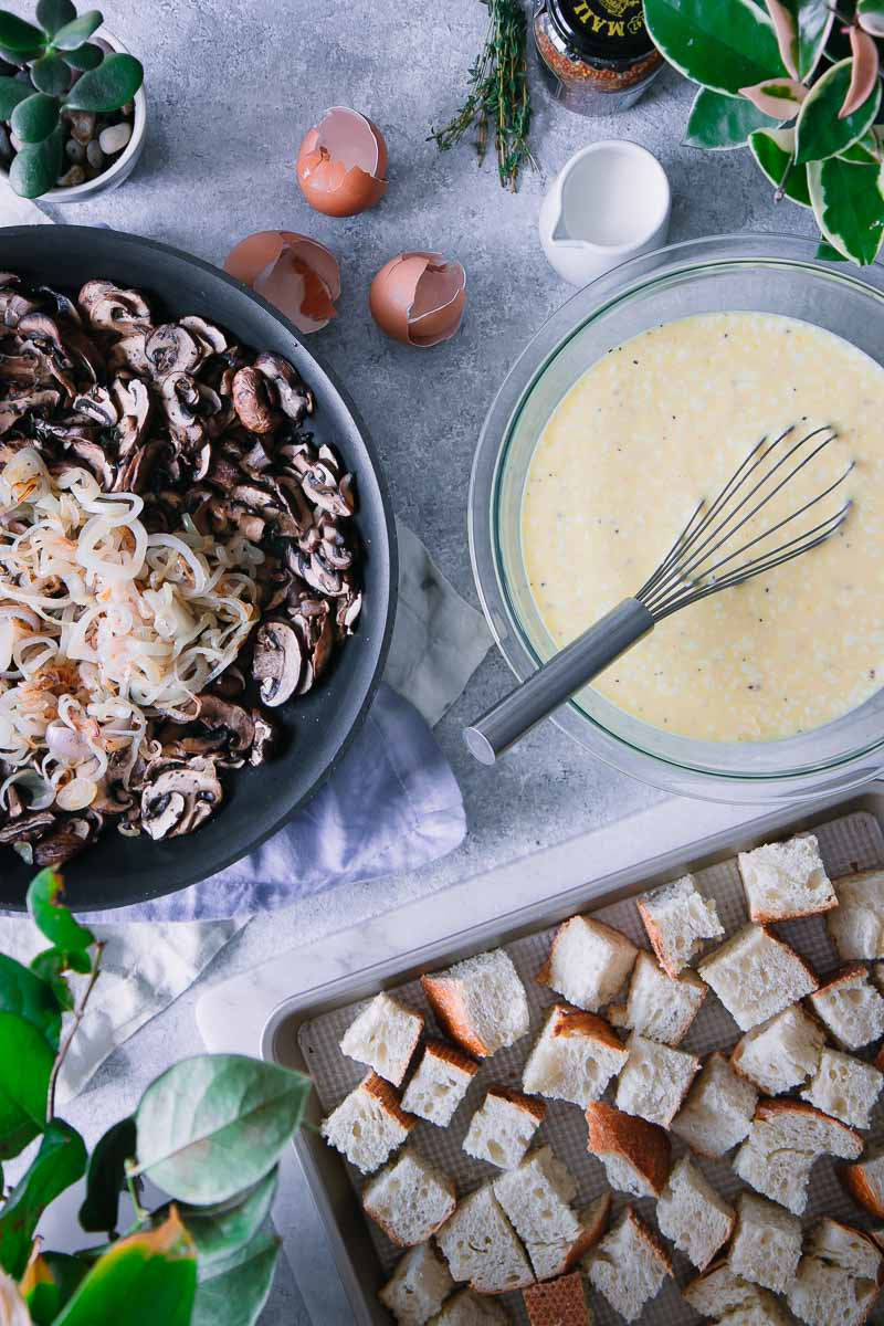 a sheetpan with toasted bread, a pan with cooked mushrooms and shallots, and a bowl with eggs and cream with a whisk, all on a blue table with napkins