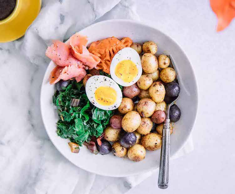breakfast bowl with roasted potatoes, greens, smoked salmon, and a soft-boil egg