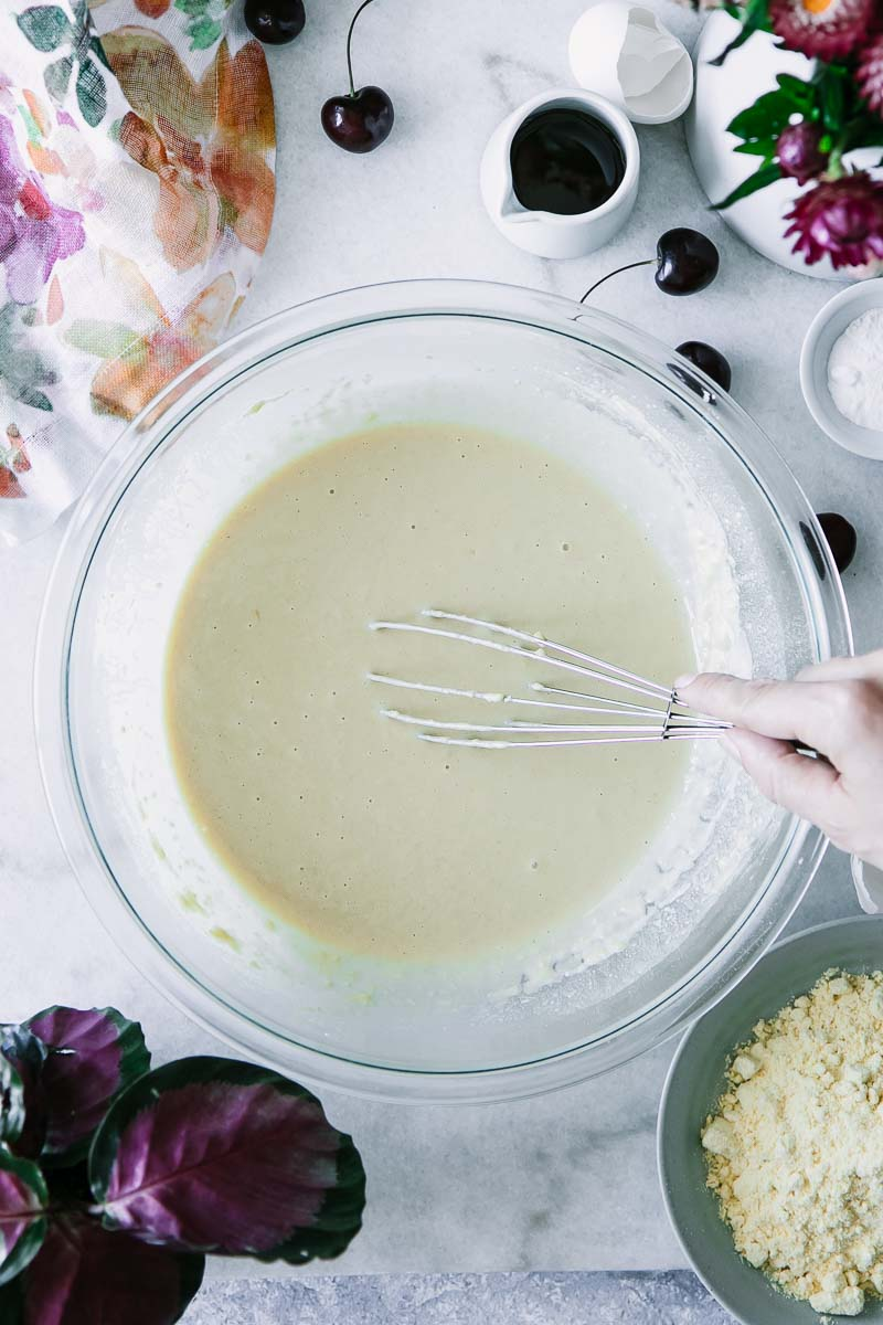 a hand mixing pancake batter on a blue table with cherries and flowers