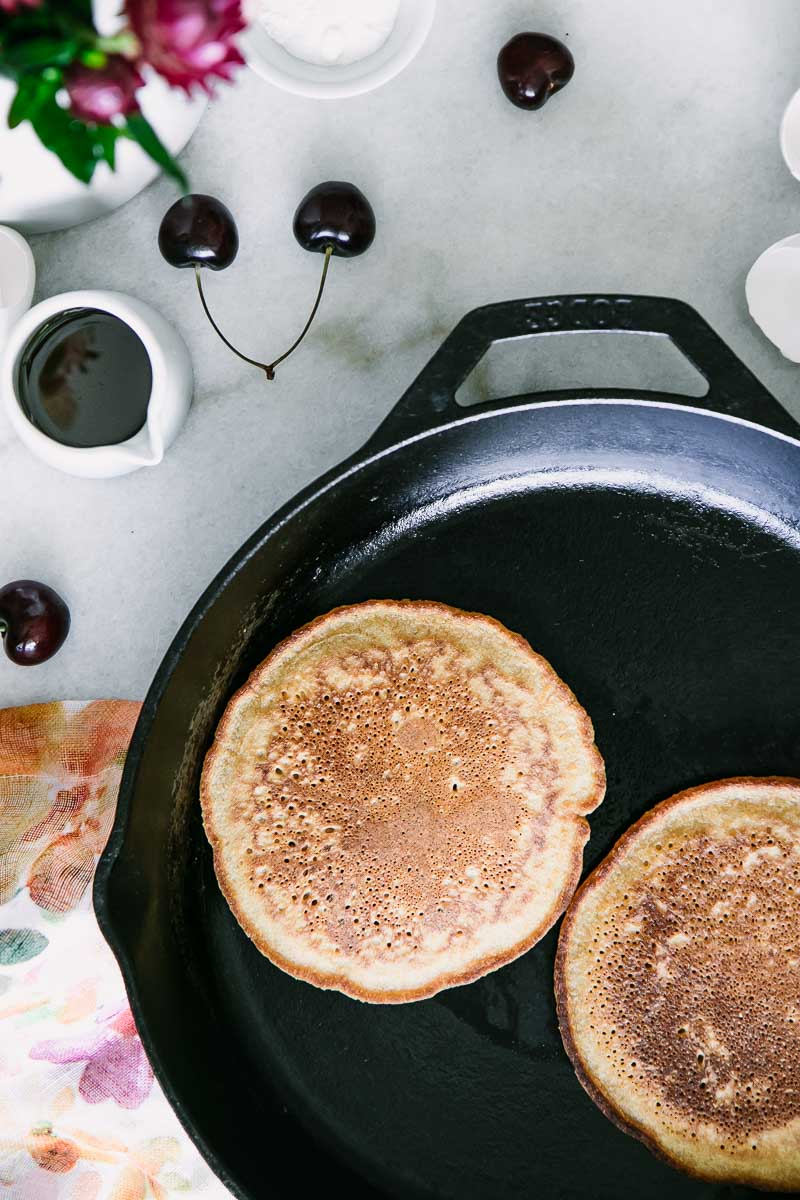 two hoecakes on a black cast iron skillet with cherries and flowers on a white table