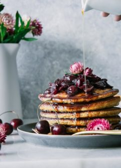 a stack of cornmeal pancakes, or hoecakes, with cherry sauce and a drizzle of maple syrup