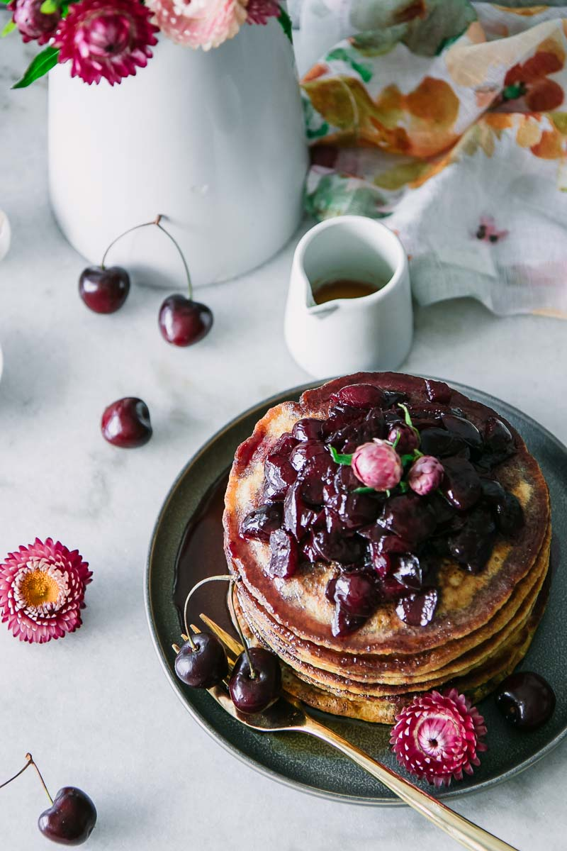a stack of pancakes with cherries on top on a white table with flowers and maple syrup