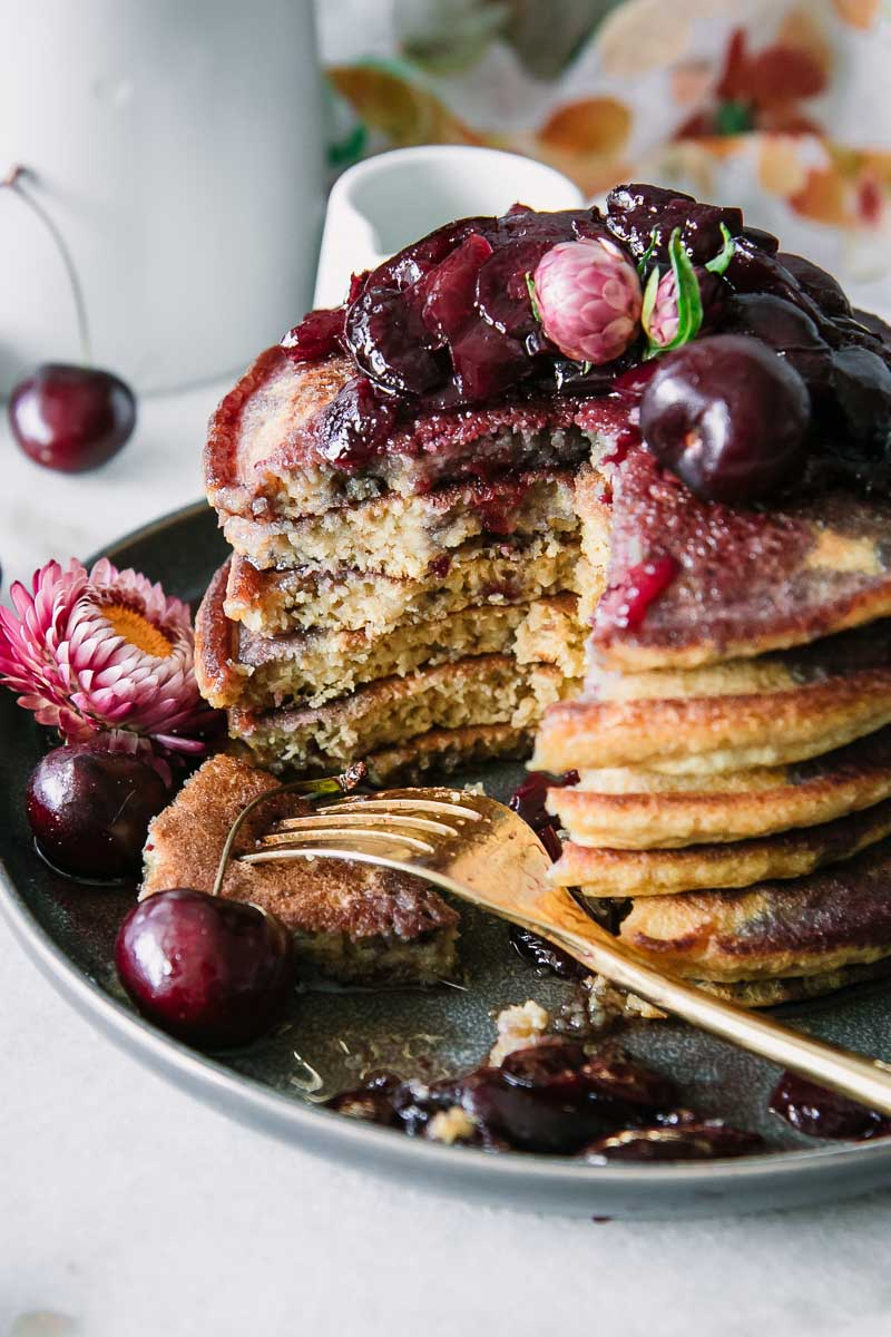 a stack of pancakes with cherries and a gold fork on a blue plate