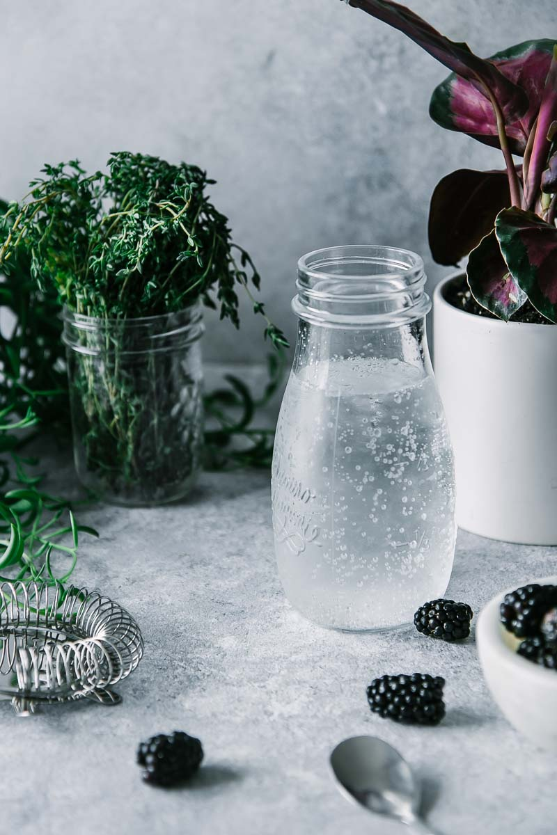 a caraffe of sparkling water, a bowl of blackberries, and a jar of fresh thyme on a blue table