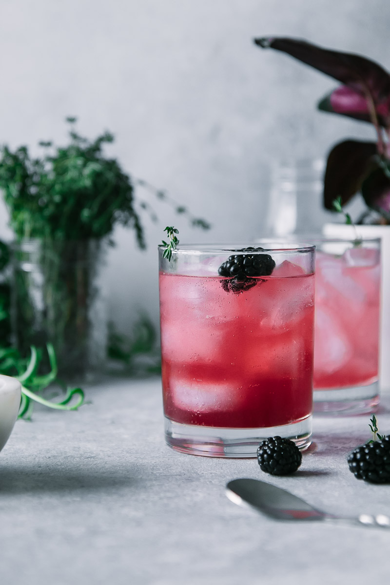 a blackberry infused sparkling water in a cocktail glass on a grey table