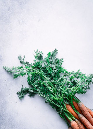 carrot tops on a blue table