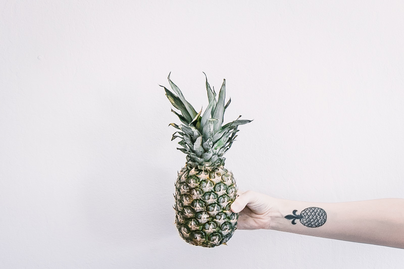 a horizontal ratio photo of a hand with a pineapple tattoo holding a pineapple with a white background