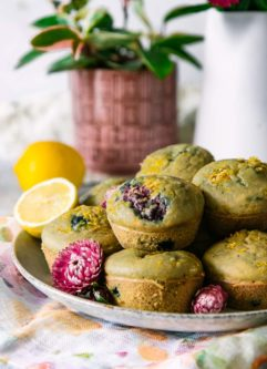 a plate with stacked lemon berry muffins and flowers on a white table