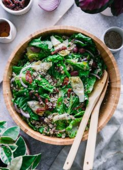 a wooden salad bowl with romaine lettuce, red onion, kalamata olives, and quinoa on a white table.