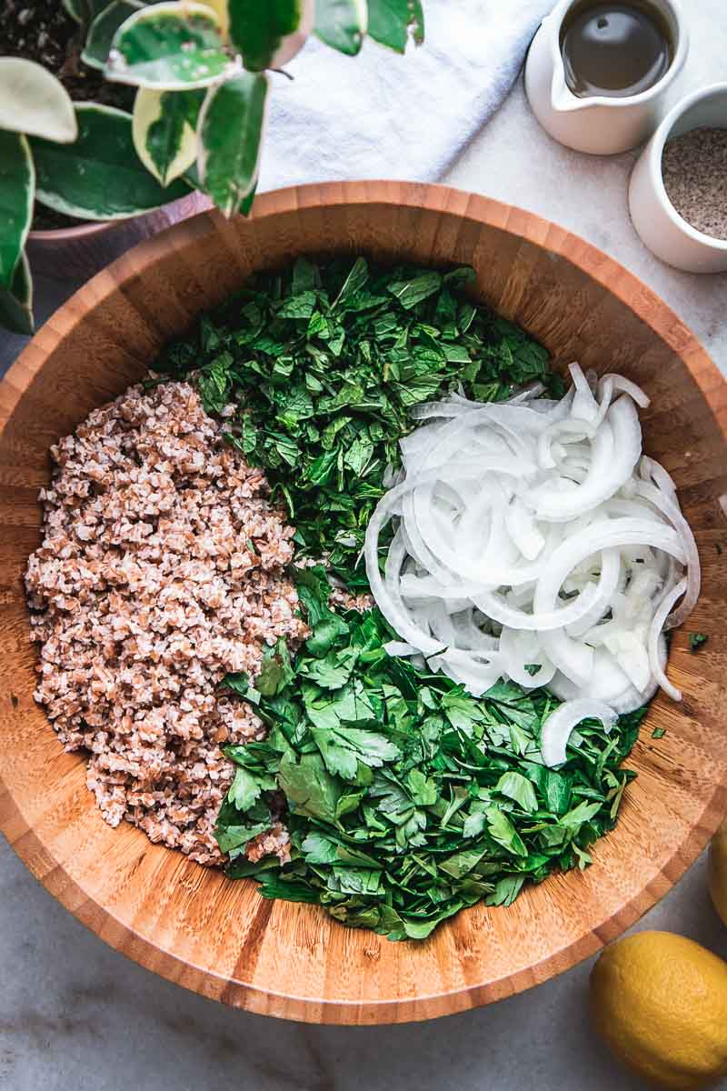 a wooden mixing bowl filled with bulgur, chopped onion, and fresh parsley and mint for a tabbouleh salad