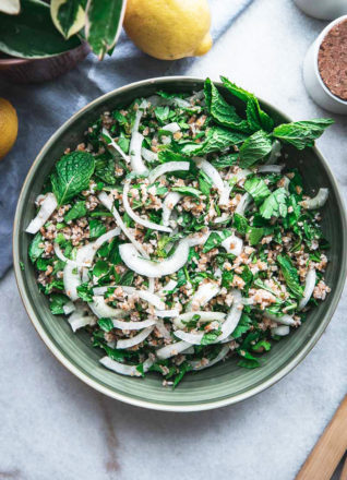 a green bowl with bulgur tabbouleh, mint, and parsley and two lemons on a white table