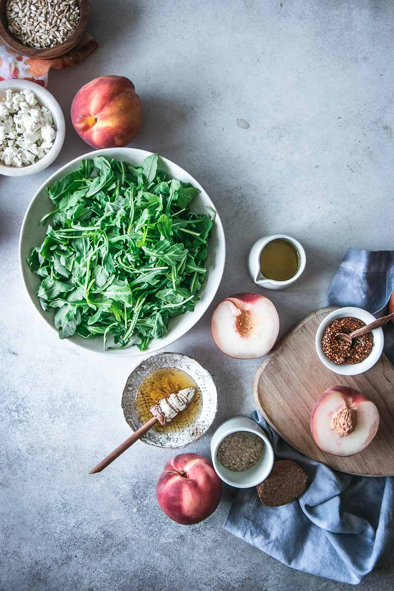 a flatlay photo of summer grilled peach salad ingredients in bowls on a blue table, including arugula, peaches, honey, sunflower seeds, goat cheese, dijon mustard, olive oil, and salt