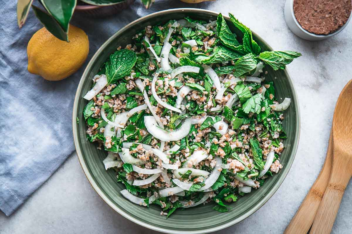 a green bowl with traditional tabbouleh with bulgur, onion, parsley, and mint on a white table with a blue napkin and lemons