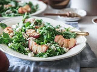 a white plate with a salad with grilled peaches, arugula, and goat cheese on a white table with a peach and a bowl of honey