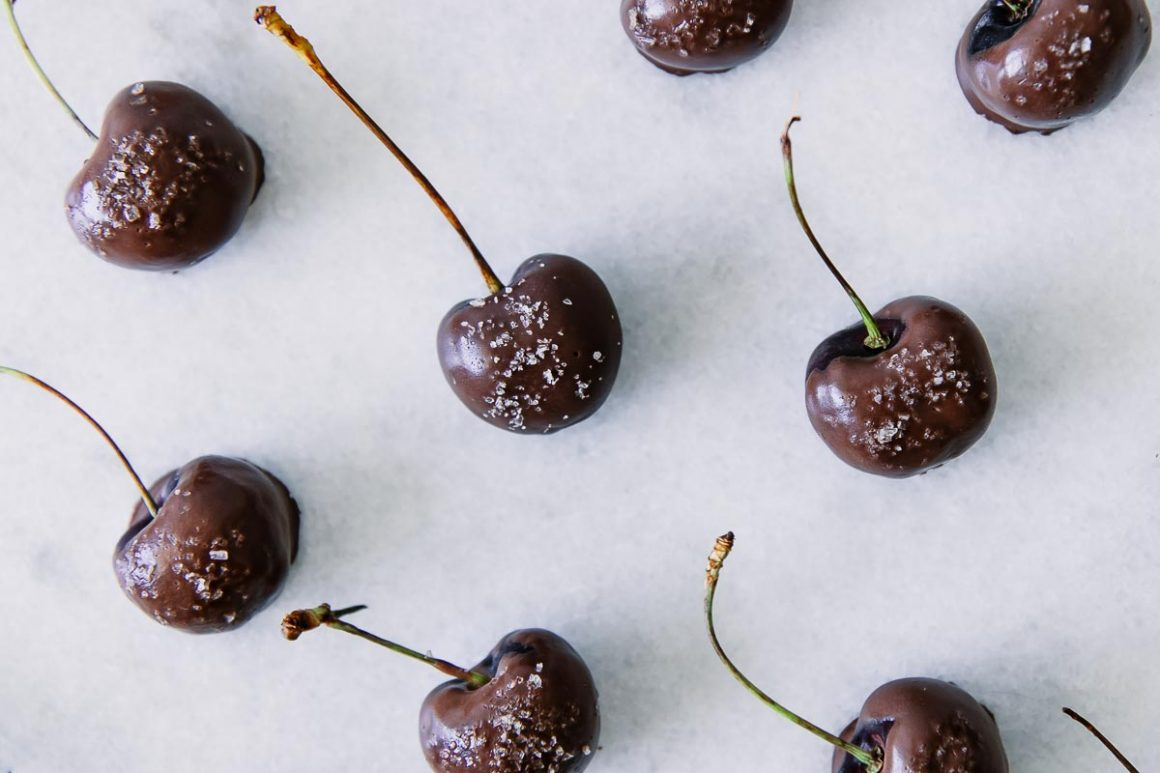 dark chocolate covered cherries with sea salt on white marble background
