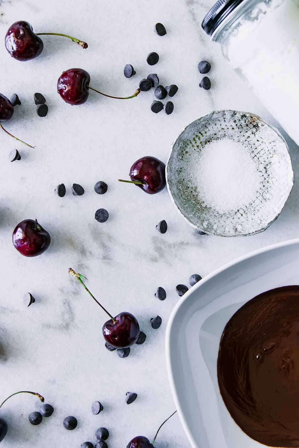 black cherries, dark chocolate chips, a bowl of sea salt, and a bowl of melted chocolate on a white marble table