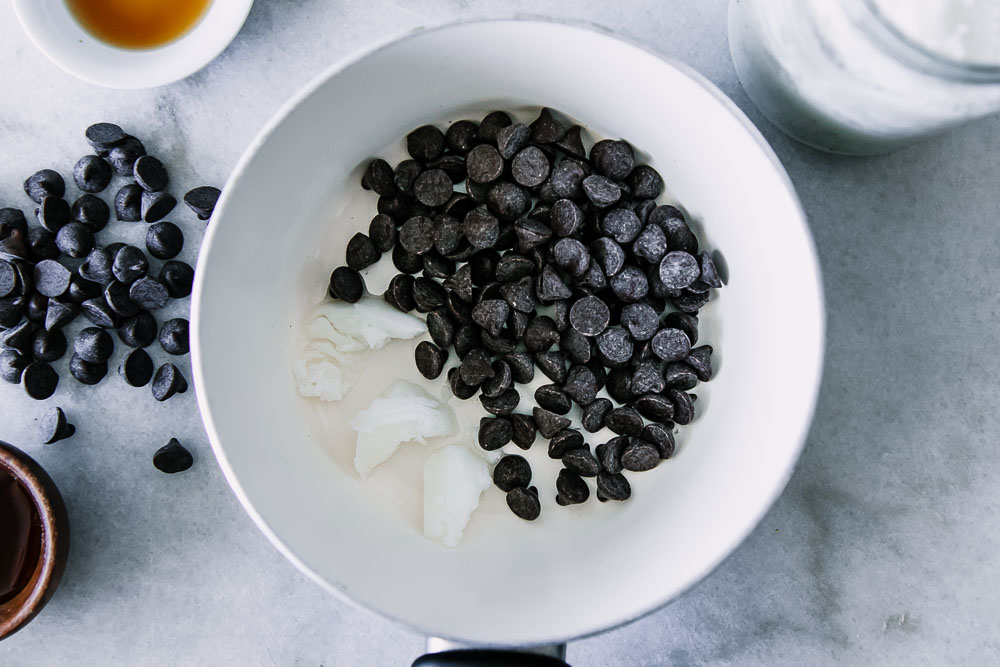 a small white saucepan with coconut oil, dark chocolate chips, vanilla, and maple syrup
