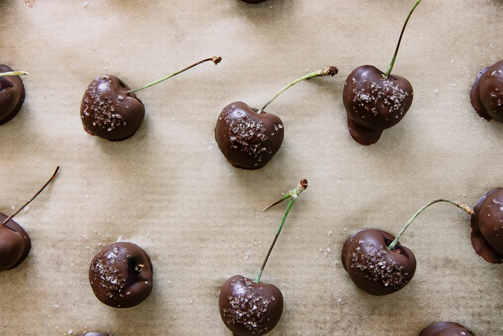 chocolate covered cherries on a sheet of waxed parchment paper on a baking sheet