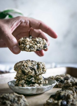 a hand picking up a chocolate chip cookie from a plate of oatmeal cookies