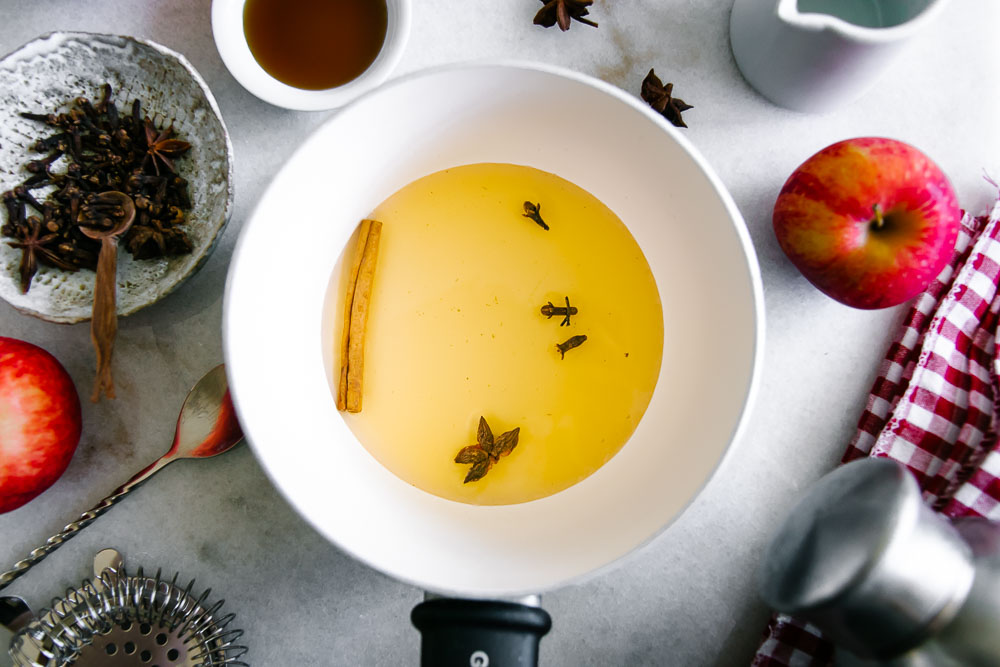 a saucepan with apple cider vinegar and infused spices like cinnamon stick, star anise, and whole cloves