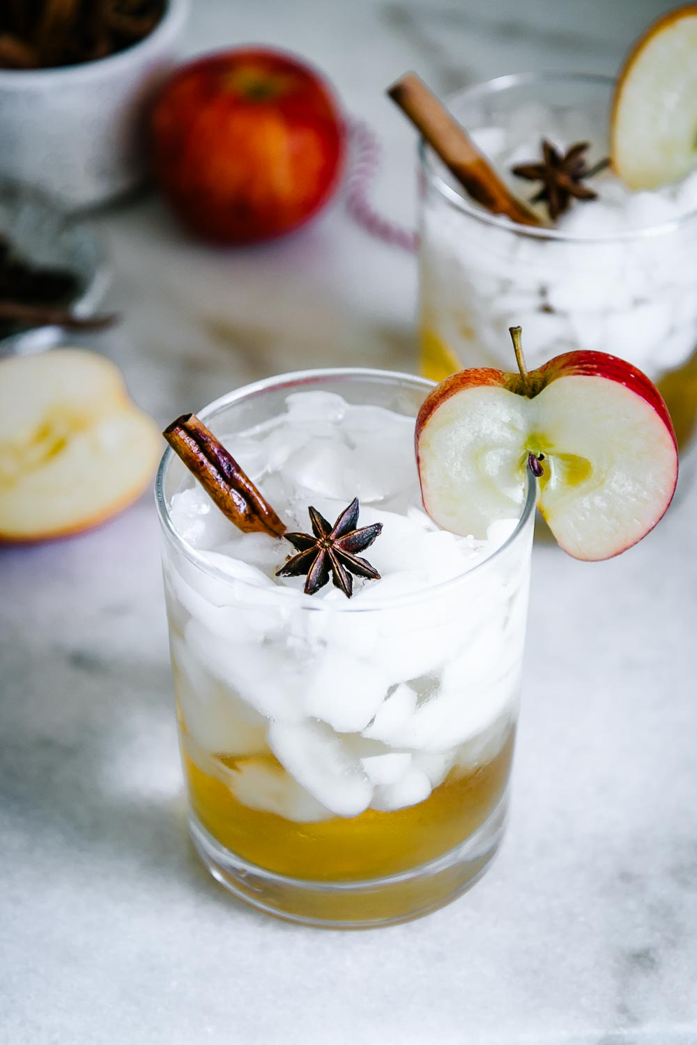 a mocktail glass with ice and apple cider sparkling water with an apple slice and a cinnamon stick