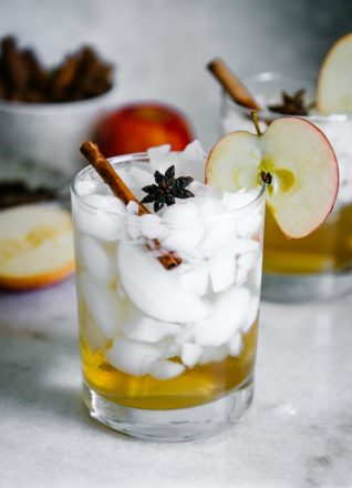 a glass with ice and apple cider vinegar and sparkline water with an apple slice garnish on a white table