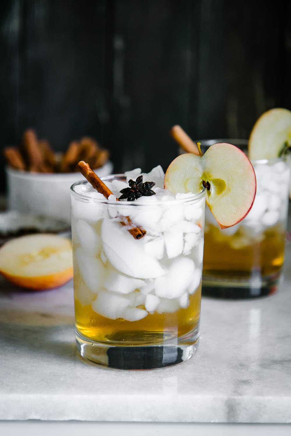 a cocktail glass with ice and apple cider spritzer on a white marble table with a black background