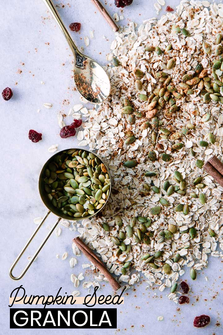 roasted pumpkin seed granola with oats and cinnamon sticks on a white table