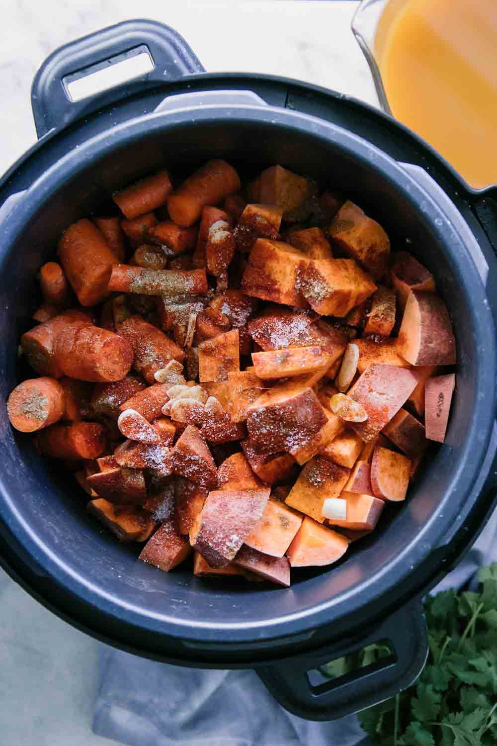 chopped sweet potatoes, carrots, and spices in an Instant Pot or pressure cooker