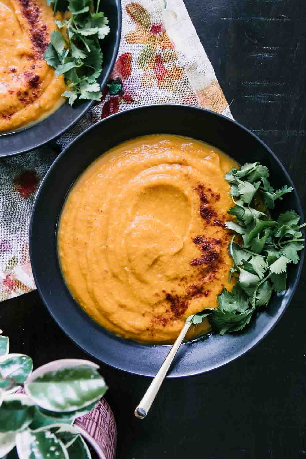 a bowl of sweet potato and carrot soup with cilantro as garnish on a wood table with a gold spoon