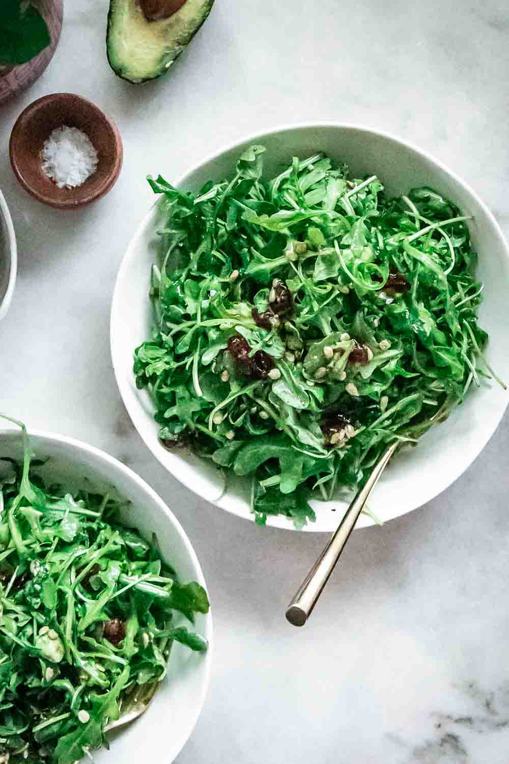arugula salad with cranberries and sunflower seeds in a white bowl on a marble table