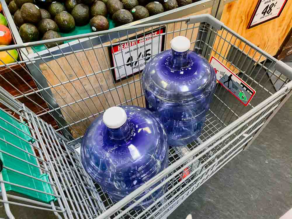 two refillable 5-gallon water bottles in a shopping cart at sprouts