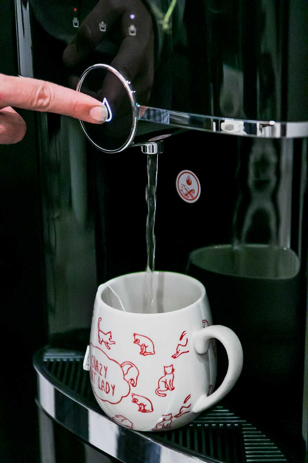 a finger dispensing water from a primo water dispenser into a coffee cup