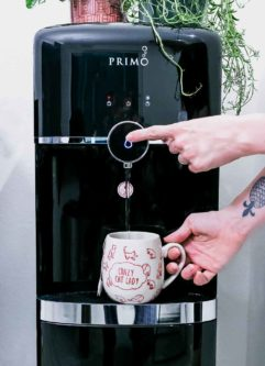 two hands dispensing water into a coffee cup from a Primo water dispenser