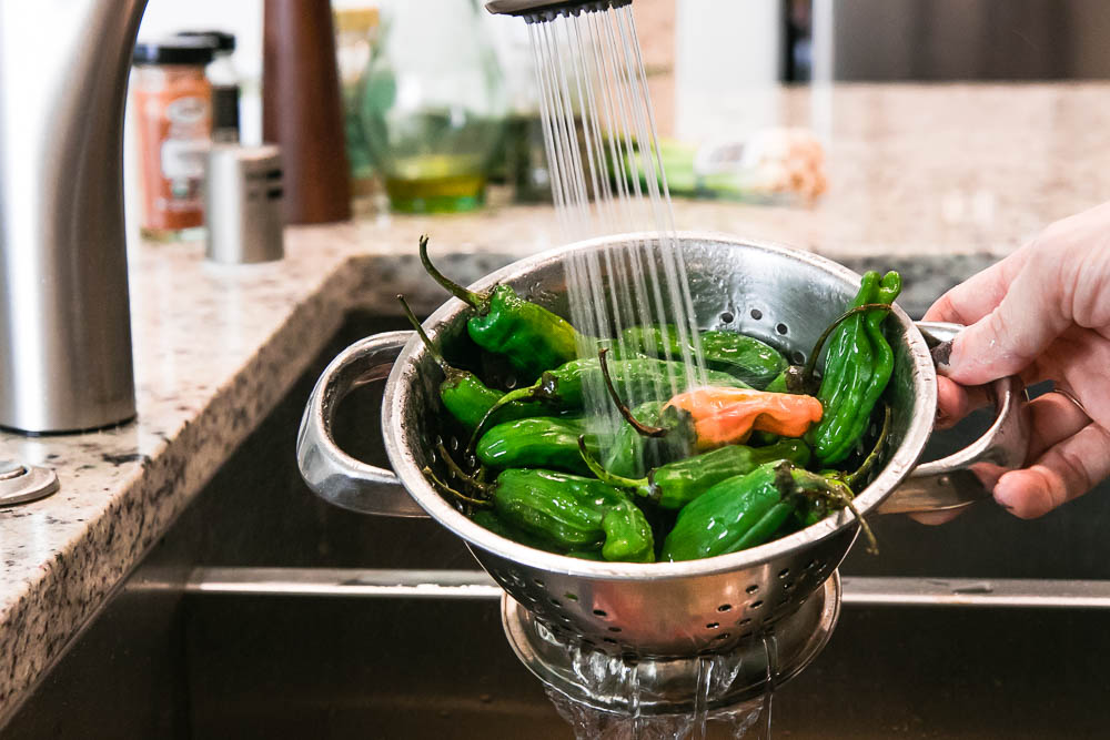 a hand washing green shishito peppers in a metal colander under running water