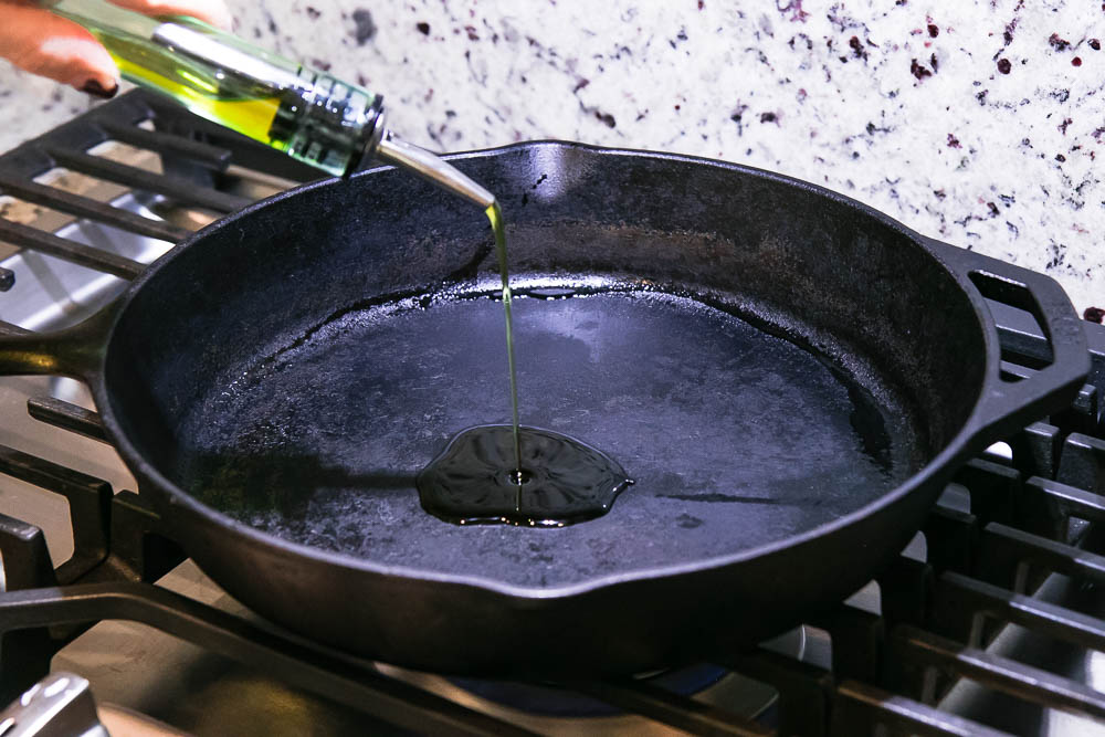 oil drizzling onto a cast iron skillet