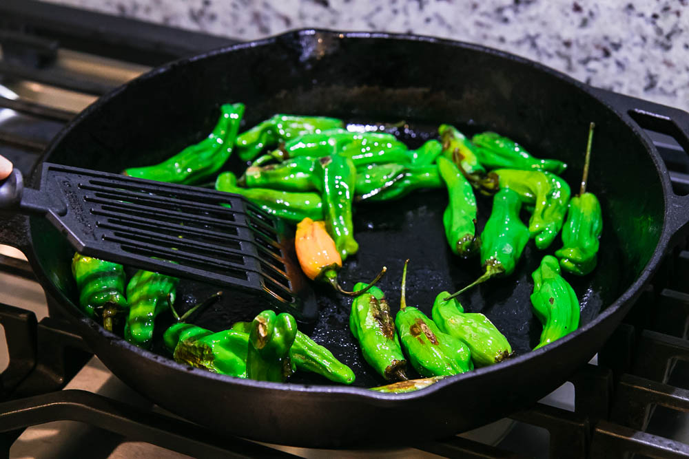 shishito peppers in a cast iron skillet with a black spatula